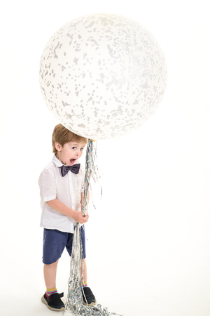Childhood. Kid with big balloon. Party mood. Celebration concept. Big white balloon. Funny boy play with flying balloon. Advertising concept. Birthday party. 写真素材