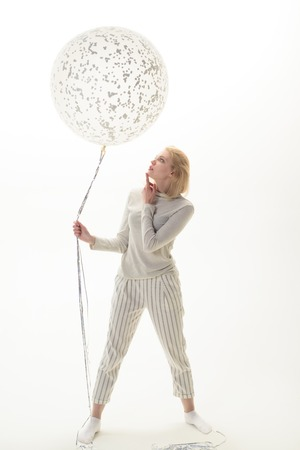 Blonde woman with big balloon. Party mood. Celebration concept. Big white balloon. Woman holds flying balloon. Advertising concept. Birthday party. Childhood. Isolated on white background.