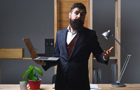 Successful businessman. Office worker. Portrait of confused bearded businessman. Businessman in suit. Man standing at table and holds laptop. Handsome bearded office worker.