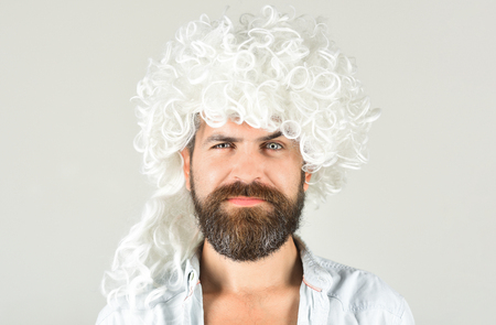 Portrait of bearded man in white wig. Bearded hipster in wig. Man in periwig. Handsome hipster. Isolated in grey background. Barbershop concept.