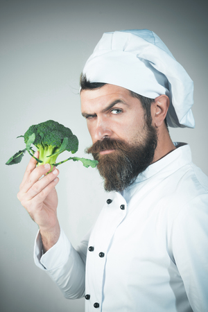 Chef with serious face in white uniform holds broccoli. Green grocery concept. Cooking and vegetarian diet concept. Cooking. Food service. Organic food. Healthy diet. Profession concept Banco de Imagens