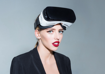 Virtual reality. Girl using VR headset. Woman in virtual reality headset. Attractive girl with makeup in virtual reality goggles at head. Future. Future technology concept. Stock Photo