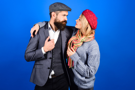Amorous happy couple. Handsome bearded man embracing girlfriend. Cute couple in warm clothes. Copy space. Trendy clothes. Fashion clothes. Autumn winter fashion. Isolated on blue background. 免版税图像