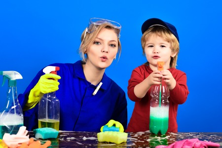 Boy holds spray on table. Child sit at wooden table with cleaning products. Cleaning activities concept. Cute little helper. Cleaning concept. Cleaning service and work concept. Banque d'images - 125056231