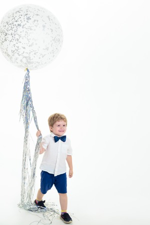 Boy in white shirt holds big balloon. Big balloon. Celebration concept. Party mood. Copy space for advertising. Smiling kid holding flying balloon. Birthday party.