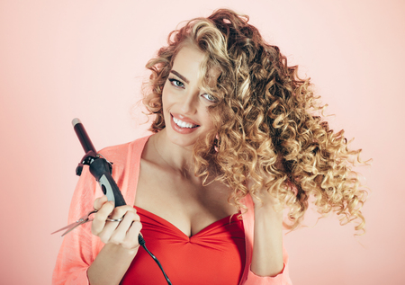Makeup and cosmetics for hair care. Hairdresser. Smiling curly hair girl holds hairdresser tool. Beauty and style. Beauty industry professional. Isolated on pink background. Hairdresser tool.