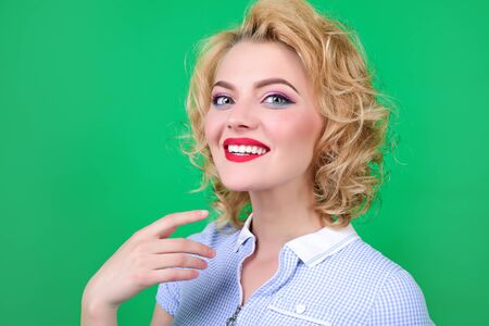 Beautiful model girl with short curly hair, red lips. Smiling girl with bright makeup and beautiful hairstyle. Care, fashion&beauty. Pin up girl, retro woman, makeup, cosmetics, skincare, hairdresser.