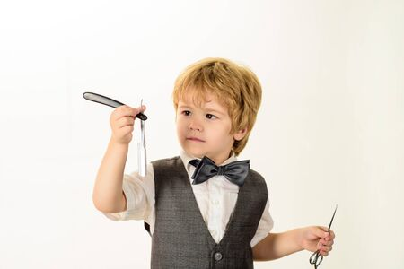 Barbershop. Little boy holds barber shop razor. Hairdresser with razor for shaving. Copy space for advertise barbershop. Barber shop equipment. Vintage razor. Beauty industry. Barber shop. Hairdresser 版權商用圖片