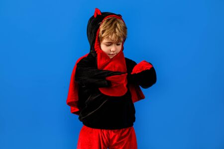 Halloween concept. Kid in monster halloween costume. Trick or treating. Cute little toddler in black&red dragon costume. Boy in dinosaur costume on Halloween. Kid dressed as dinosaur. Halloween season