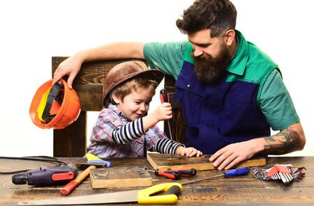 Father&son in workshop repairing. Cute boy exploring tool. Fatherhood concept. Dad&son child working with tools. Parent with busy small son. Daddy with little son in protective helmet with screwdriver Stock Photo