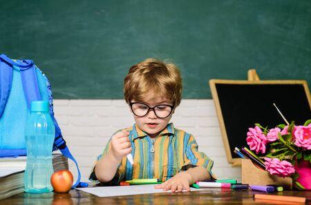 Teachers day. School boy at blackboard. Kid is learning in class. Little boy pupil at desk with school supplies. Kids school. Cute child boy in classroom near blackboard. Kid gets ready for school.