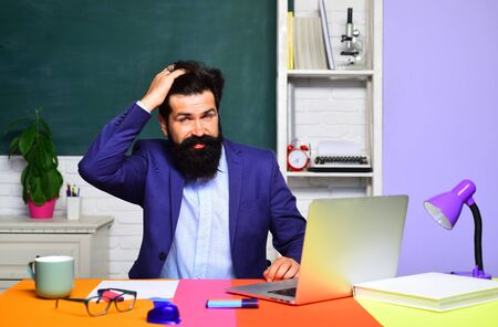 Happy male student studying in school. Good teachers enjoy teaching. Bearded professor at school lesson in classroom. Teacher is skilled leader. Teachers day. Knowledge and educational school concept. Stock fotó