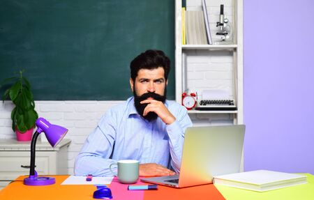Serious bearded male teacher. Student studying in classroom. Student studying in university. College student at campus. World teachers day. Teacher job. Education. Student preparing for test or exam.