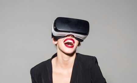Amazed attractive girl with VR device. Virtual reality goggles. Woman in VR headset. Connection, future technology, progress concept. Excited surprised woman using 3d goggles watching virtual reality. 版權商用圖片