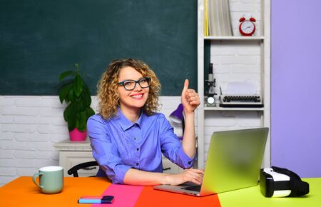 Student in college. Young teacher in glasses over green chalkboard background. High school concept. Teacher is skilled leader. Learning and education. Exam in college. Female student in university.
