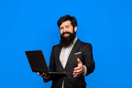 Smiling bearded man with laptop. Businessman working with pc at office. Happy bearded man with computer. Bearded business man holds laptop. Handsome businessman hold laptop. Confident business expert. Stock Photo