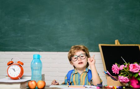Clever kid writing at desk. Schoolboy. Elementary school student write at workplace. Cute child boy doing homework. Kid enjoy learning. Home schooling. Back to school. Little boy at school lesson. Stockfoto