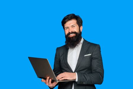 Happy bearded man with laptop. Smiling business expert with pc. Businessman works with notebook at office. Businessman with computer. Bearded businessman hold laptop. Handsome businessman hold laptop. Stock Photo