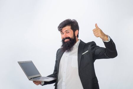 Businessman with pc shows thumb up. Business man working with laptop. Handsome businessman working with notebook in office. Office, business, technology, internet. Man with laptop computer at office.