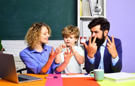 Cute pupil and his parents making schooling work. Parenting. Happy family. Mom and dad helps child boy. First time to school. Happy family schooling math together. Children education. Pupil education.