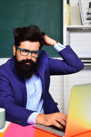 Male university student works with laptop in classroom. Student in glasses learning in auditorium. Teacher job. Profession, learning, knowledge. High school. Education, tutoring and teacher concept.