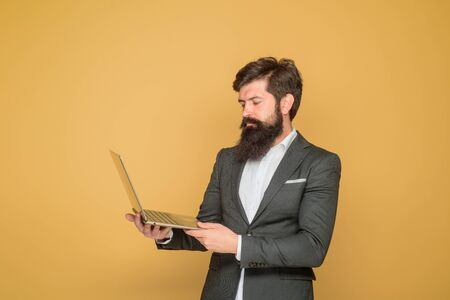 Confident business expert. Serious bearded man with computer. Handsome businessman holds laptop. Businessman working with pc at office. Businessman with laptop. Bearded business man holds laptop