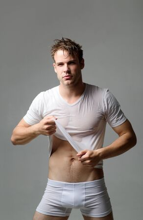 Underwear. Sexy guy take off wet shirt. Sexy guy in wet white shirt. Man in white underwear. Man in underwear isolated. Black Friday. Men in boxer shorts. Fitness model. Sale. Discount. Stock Photo - 126862107