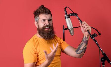 Uomo barbuto che canta con il microfono. Cantante brutale del ragazzo barbuto con il microfono sul palco. Vocalist maschio che canta nello studio di registrazione. Canto del cantante nel microfono a condensatore. Concerto e concetto di musica Archivio Fotografico