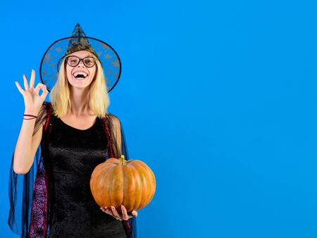 Halloween party. Happy halloween girl shows sign ok. Halloween witch in glasses with magic pumpkin. Magic hat. Sexy wizard. Secrets magic. Holiday halloween with carnival costumes. Witch. Wizard suit.
