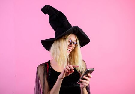 Beautiful sensual sexy woman with cellphone. Message. Blonde woman witch using mobile phone, smart phone. Modern technology and leisure concept. Woman in black dress and witch hat using smartphone. Stockfoto