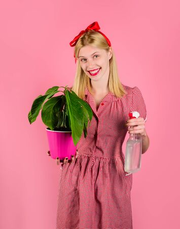 Woman take care of flowers. Girl cultivating flowers. Woman with spray bottle spraying houseplants. Watering concept.