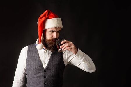 Santa man drinking glass of whiskey. Serious man in Santa hat drinking whiskey. Man in waistcoat tasting glass of whisky. Handsome bearded businessman hold glass of whiskey. New year party. Copy space