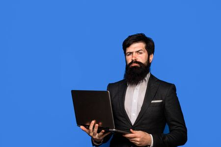 Businessman working on computer laptop online. Business, internet, technology concept. Serious business man with notebook at office. Stylish bearded businessman in suit with modern laptop. Copy space.