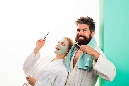 Couple. Woman applying mascara, man brushing teeth. Bearded man in bathrobe brushing teeth. Morning preparation. Girl with cosmetic mask on face applying mascara. Wife and husband preparing for work.