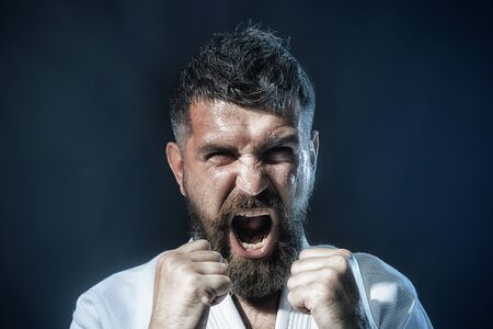Man practicing karate martial art. Sportsman exercising karate martial art combat, self defense. Bearded man in traditional kimono practicing karate, martial arts, mixed martial arts, MMA, kick boxing Фото со стока