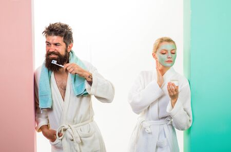 Health. Relationship. Family life. Couple. Husband and wife. Morning routine. Morning procedures. Morning treatments. Woman with cosmetic facial mask. Bearded man with with toothbrush cleaning teeth.