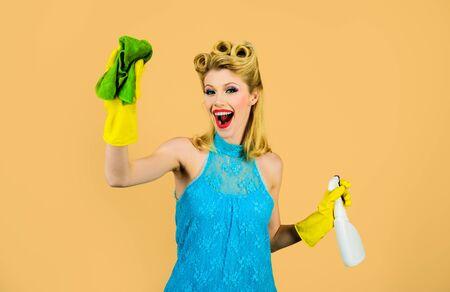 Firma sprzątająca. Dziewczyna czyszczenia szmatką i sprayem do butelek. Gospodyni gotowa do prac domowych. Piękna kobieta trzyma prochowiec i spray. Narzędzia do czyszczenia. Szczęśliwa gospodyni retro. Sprzątać. Czyszczenie szałowy kobieta.