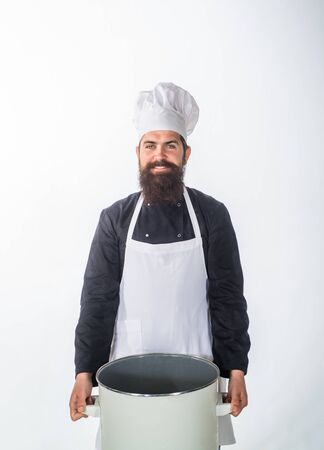 Bearded chef in kitchen holds big pot. Cook in white apron with pot. Master chef. Cooking, culinary, cuisine. Food preparation concept. Chef man prepares meal. Professional cook holds kitchen utensil. Stock Photo