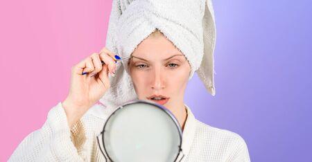 Schönheitspflege der Augenbrauen. Schönheitswerkzeuge. Frau zupft Augenbrauen im Spiegel. Augenbrauen epilieren. Frau mit Pinzette. Make-up-Prozess für Mädchen. Korrekturverfahren im Schönheitssalon. Standard-Bild