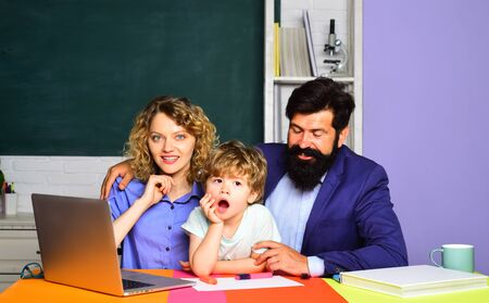 Happy schoolboy at lesson. September 1. Child from elementary school with parents in school. School education. Beginning of lessons. Ready to study. Cute pupil and his father and mother in classroom.