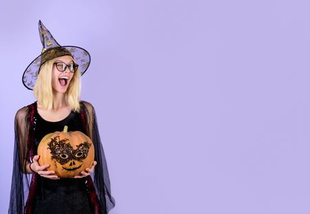?heerful girl in black witch costume with pumpkin on party. Jack-o-lantern. Happy halloween concept. Halloween costume party and Halloween decor. Winking sexy witch in glasses.Copy space for advertise