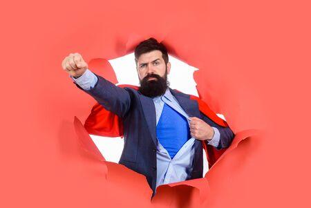 Par le papier. Homme barbu regardant à travers le papier. Super-héros en cape rouge montrant une chemise bleue. Super-héros. Banque d'images