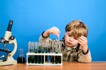 Chemistry. Science. Experiment. Education. Study. Biology. School. Surprised boy working with test tubes. Little kid with test tubes. Back to school. September.