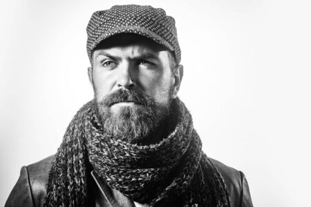 Bearded hipster man in jacket, wool cap, knitted scarf. Stylish brutal bearded man wears hat, scarf&leather jacket. Guy with beard, mustache in tweed cap&leather coat. Macho in autumn stylish clothes.