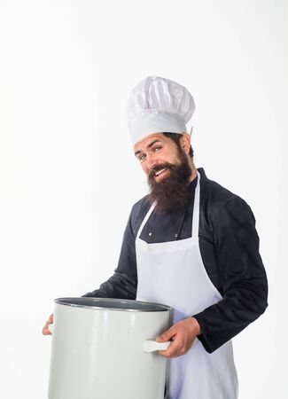 Professional cook holds kitchen utensil. Bearded chef in kitchen holds big pot. Cook in white apron with pot. Master chef. Cooking, culinary, cuisine. Food preparation concept. Chef man prepares meal.