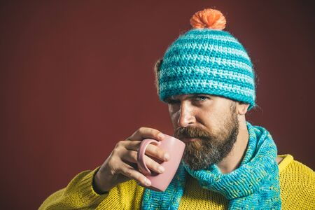 Attractive bearded man in trendy sweater hold cup/mug with hot beverage. Bearded man drinking coffee. Handsome guy drinks coffee. Stylish man drinking tea from cup. Businessman drinking coffee in cafe 免版税图像