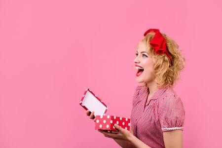 Attraente ragazza pinup con confezione regalo in mano. Ragazza felice in stile retrò con confezione regalo presente. La bella donna in vestito rosso tiene la scatola attuale aperta. Natale, capodanno, compleanno, San Valentino Archivio Fotografico