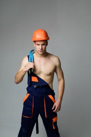 Industrial worker, plumber in hard hat with plumber tools. Plumber tools and accessories. Serious plumber holds screw-wrench in bathroom. Civil engineer working on construction site, foreman at work.