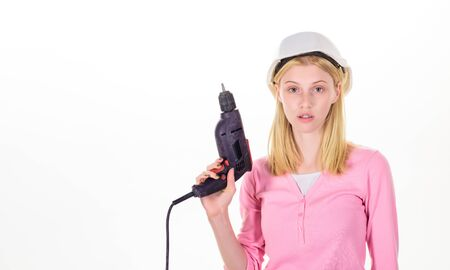 Woman builder worker with drill. Young woman holds construction drill. Girl in hardhat with drill. Female construction worker with electric screwdriver. Woman in safety helmet with drill machine. Reklamní fotografie
