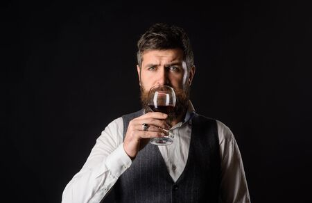 Man in waistcoat holds glass of red wine. Bearded man tasting glass of wine. Winetasting and degustation concept. Sommelier tasting red wine. Handsome man with beard drinking red wine with enjoyment.